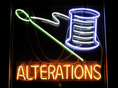 Neon sign depicting needle and spool of thread in window of dry cleaners
